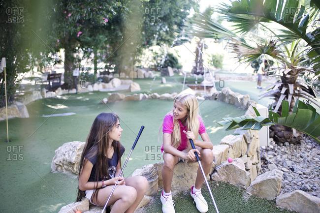 Girls talking during minigolf game