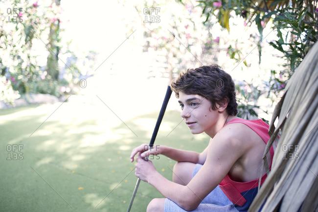 Boy sitting during minigolf game