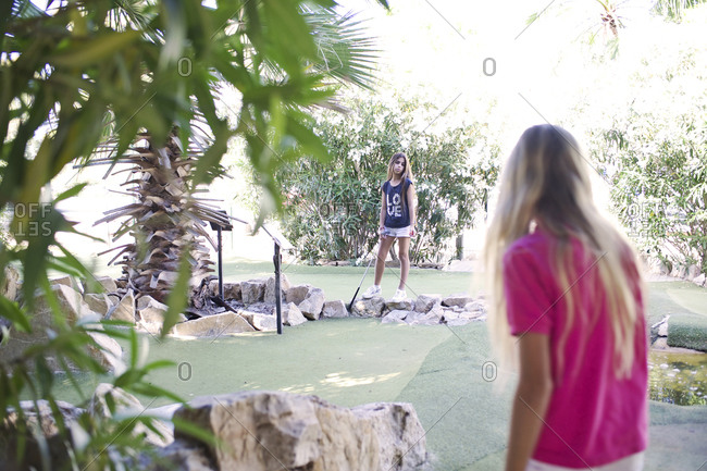 Two girls standing on minigolf course