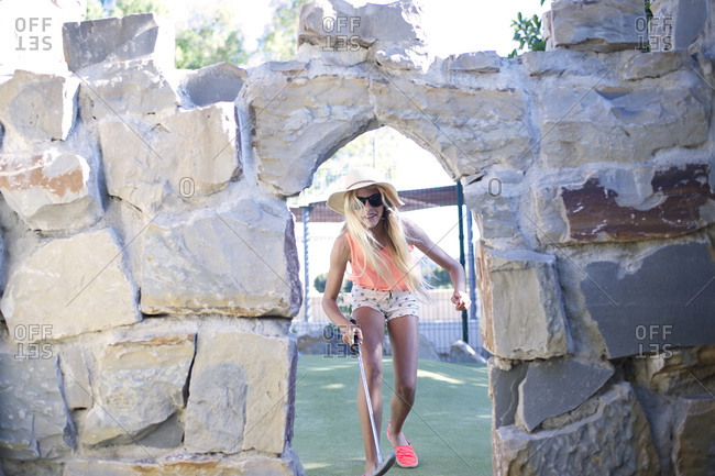 Girl looking through minigolf obstacle