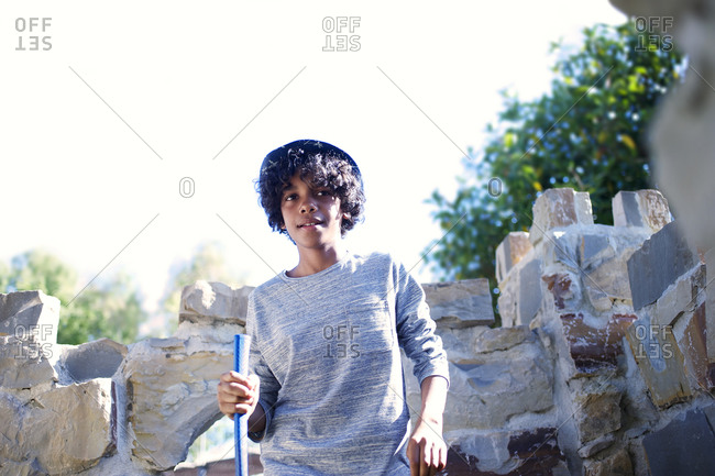 Adolescent boy standing by minigolf obstacle