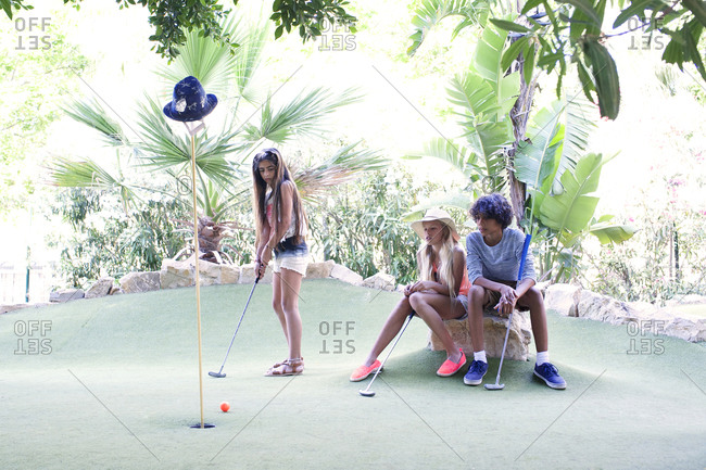Adolescents playing minigolf game