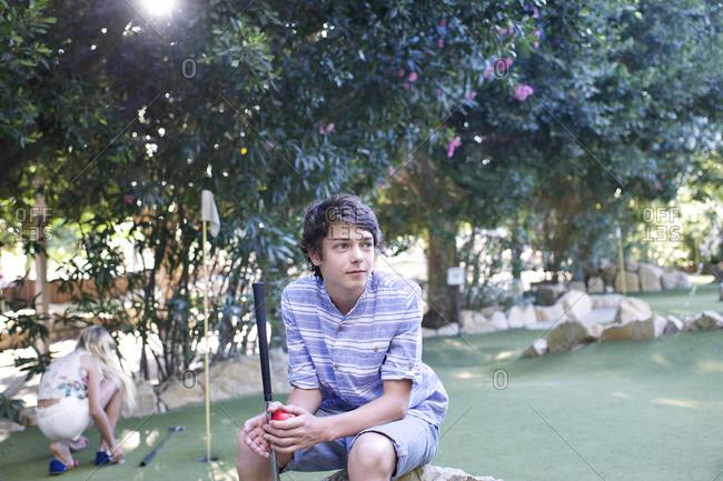 Adolescent boy sitting during minigolf game