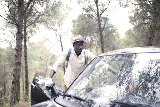 Man leaning on car in rural setting