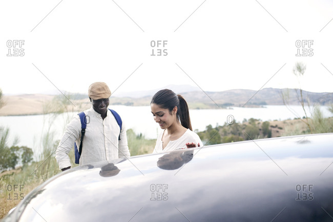 Young couple by car in wilderness setting