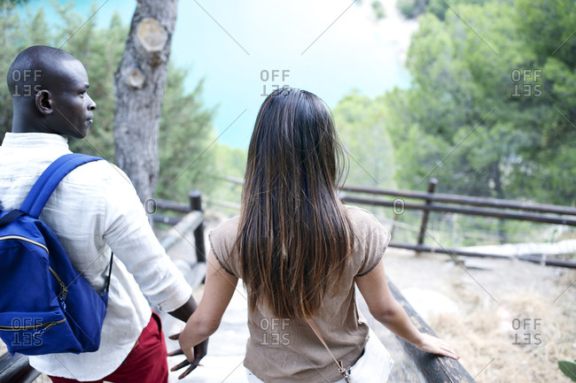 Young couple going down hillside steps