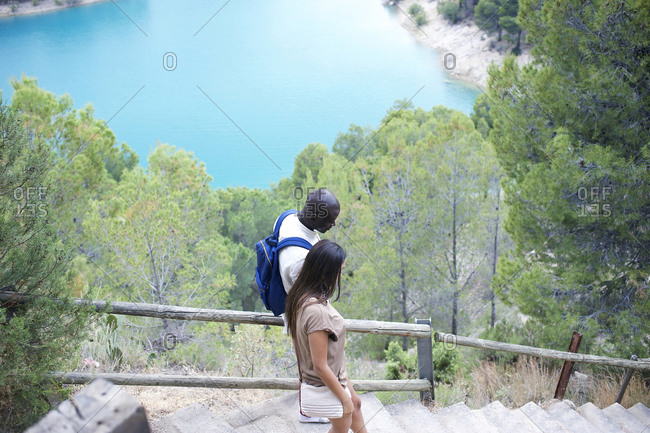 Young couple going down lakeside stairs
