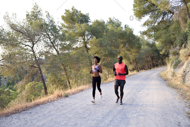 Athletic couple running on rural road