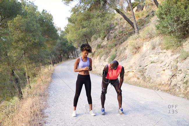 Athletic couple setting time on rural road