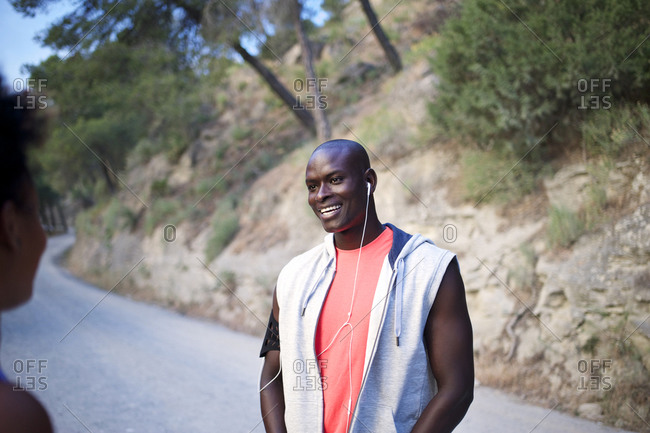 Athletic man smiling at friend on rural road