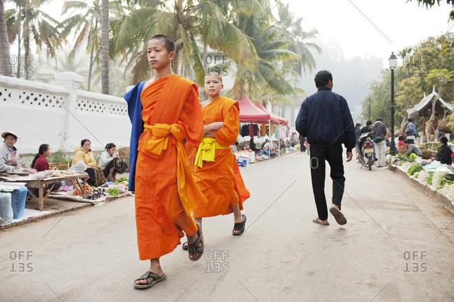 Luang Prabang, Laos - January 27, 2009: Buddhist monks walk through the morning market, Luang Prabang, Laos