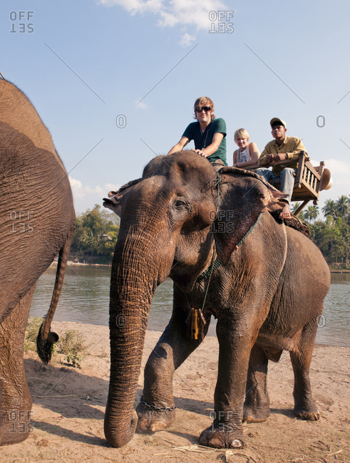 Luang Prabang, Laos - January 31, 2009: Couple on elephant ride on Khan River, Luang Prabang, Laos