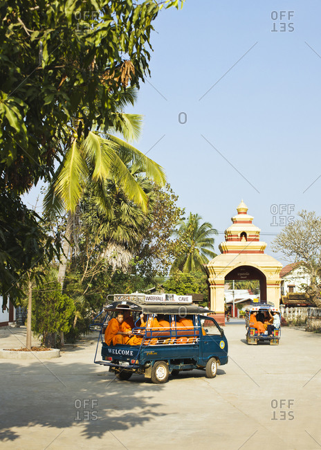Luang Prabang, Laos - January 30, 2009: A car load of monks drives off from Wat Manoran, Luang Prabang, Laos