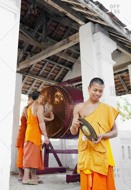 Luang Prabang, Laos - January 26, 2009: Monks beat the drum at Vat Paphaimisaiyanaram at dusk, Luang Prabang, Laos