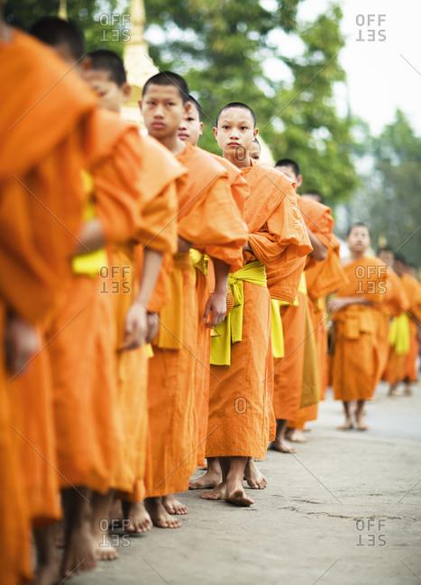 Luang Prabang, Laos - January 26, 2009: Monks going out for alms at sunrise, Luang Prabang, Laos