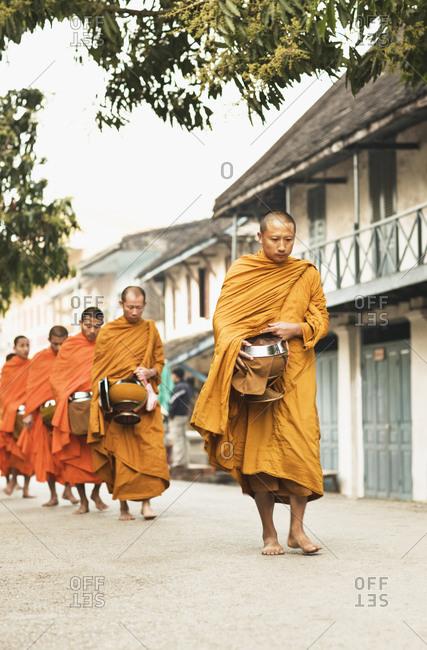 Luang Prabang, Laos - January 26, 2009: Monks in line for alms at sunrise, Luang Prabang, Laos