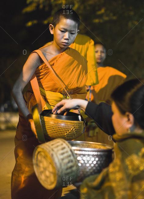 Luang Prabang, Laos - January 26, 2009: Monks receiving alms at sunrise, Luang Prabang, Laos