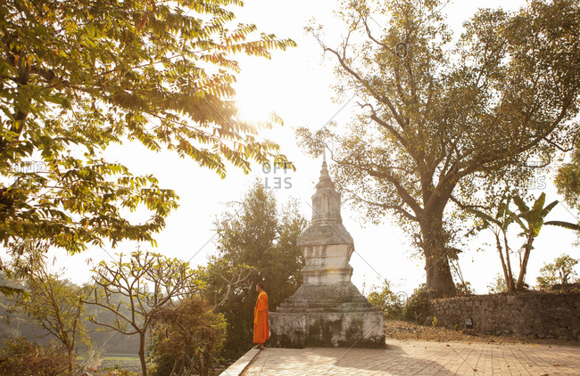 Luang Prabang, Laos - January 26, 2009: Monk by Wat Siphoutthabat Thipphuramm at dawn, Luang Prabang, Laos