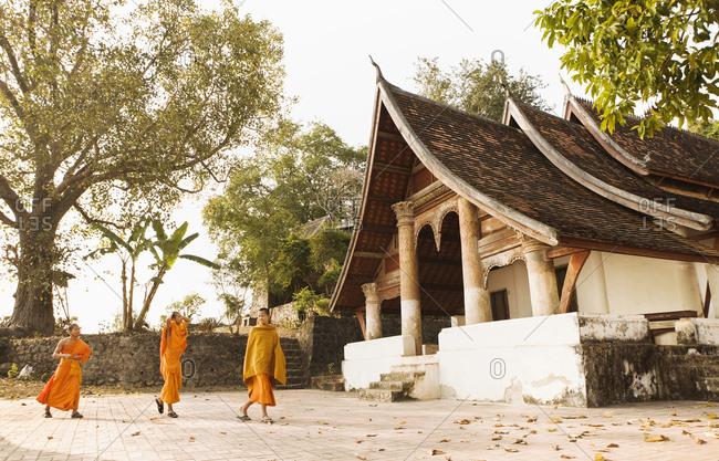 Luang Prabang, Laos - January 26, 2009: Young monks by Wat Siphoutthabat Thipphuramm at dawn, Luang Prabang, Laos