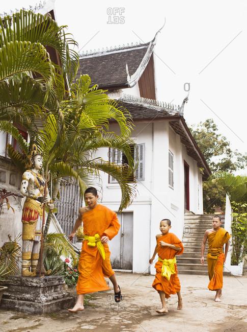 Luang Prabang, Laos - January 29, 2009: Novice monks run to breakfast at Wat Nong Sikhunmeuang, Luang Prabang, Laos
