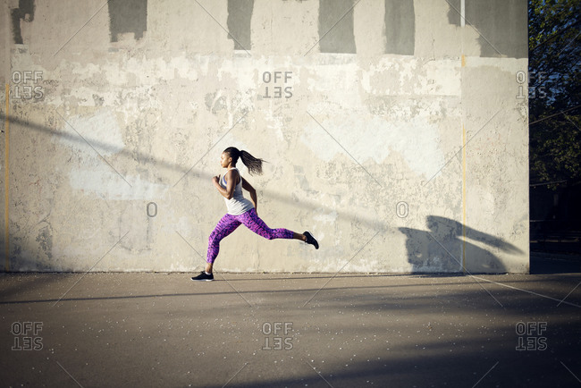 A runner sprints in an urban park