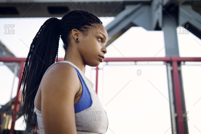 An athlete with piercings stands on a bridge