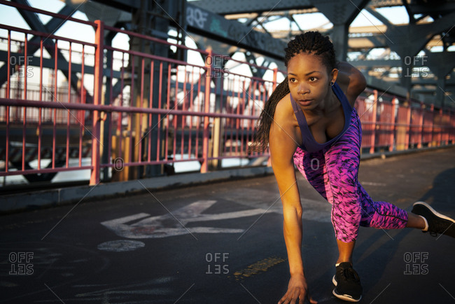 A runner crouches to sprint on a bridge