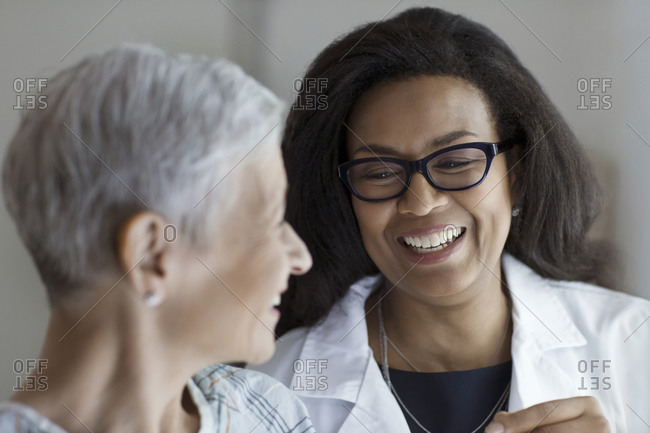 A doctor laughs with a patient