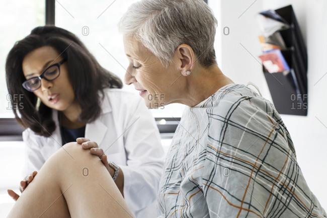 A doctor examines her patient's knee