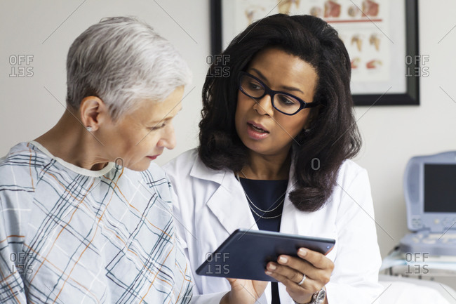 A doctor reviews information with her patient on a tablet