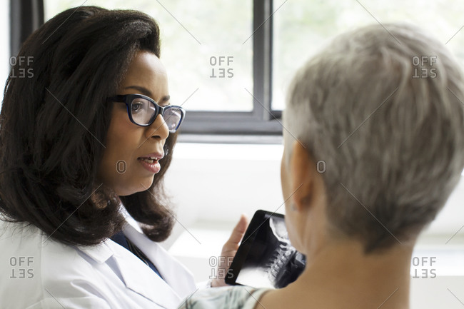 A doctor discusses an x-ray with a patient