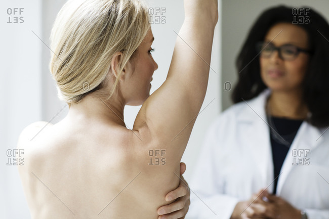 A young woman raises her arm for the doctor