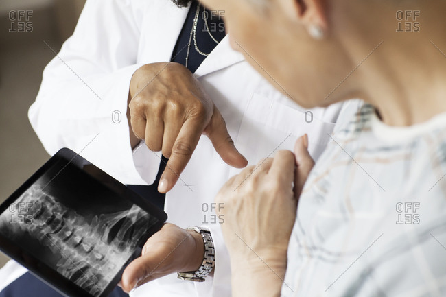 A doctor shows a patient an x-ray