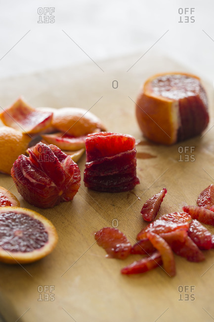 Blood orange segments on a wooden cutting board