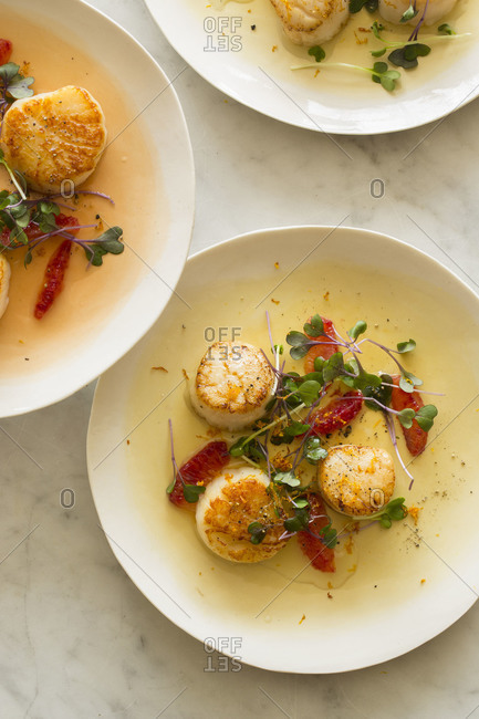 Seared scallops with blood orange segments and micro greens