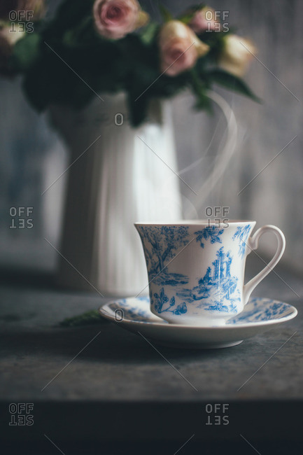 Tea cup and wilted roses