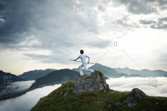 Woman exercising stick fighting on mountain top