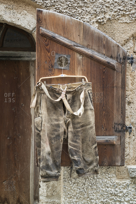 Short leather trousers hanging on shutter for sale