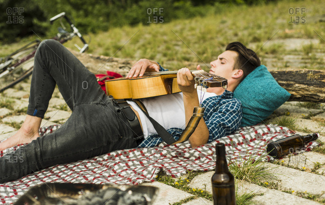 Relaxed young man playing guitar outdoors