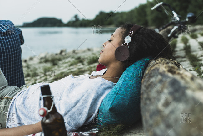Relaxed young woman with headphones by the riverside