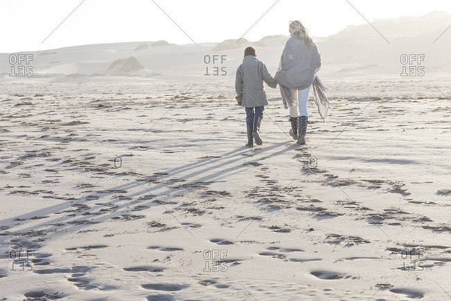 Mother and her son walking on the beach