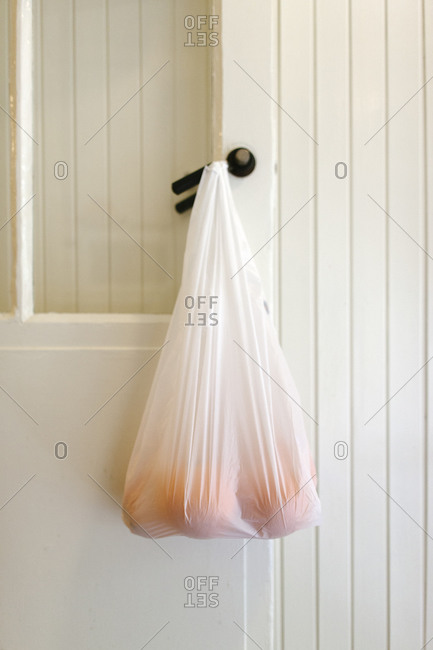 A bag of oranges hanging from a door knob in a kitchen