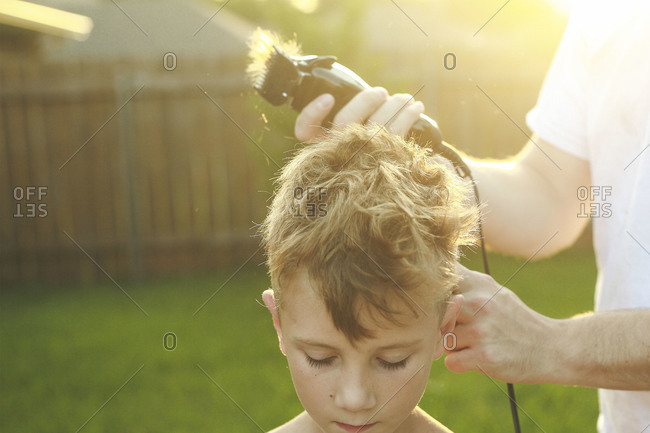 Father trimming his son's hair