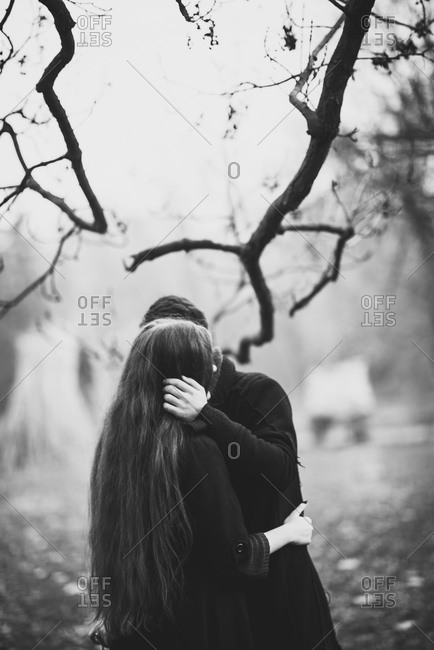 A couple hugs in the woods