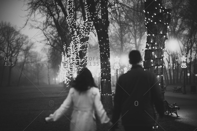 A couple walks down a decorated park path