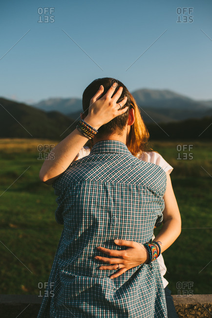 A couple kisses in a field