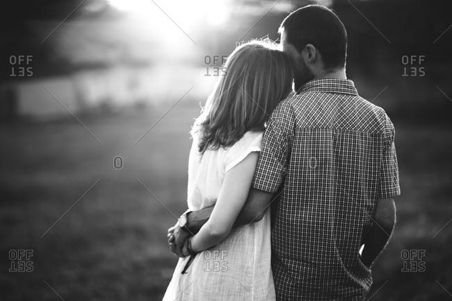 A couple hugs in a field