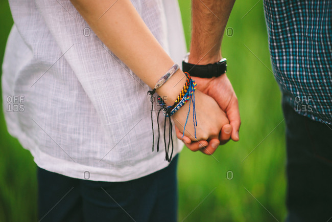 A woman with friendship bracelets holds hands with her boyfriend