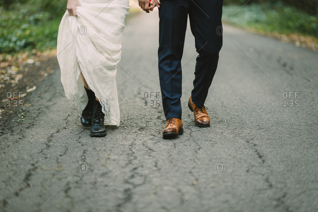 A bride in combat boots walks down a  path with her husband