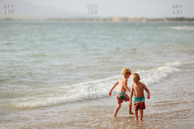 Two boys stomp through the water at the beach